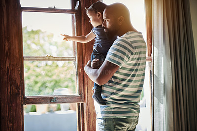 Buy stock photo Cropped shot of an adorable little boy pointing outside while looking through the window with his dad at home