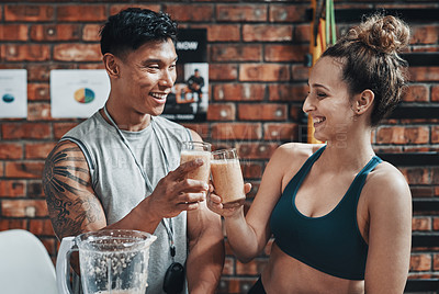 Buy stock photo Cropped shot of two young sportspeople making a toast with milkshakes while working in a gym