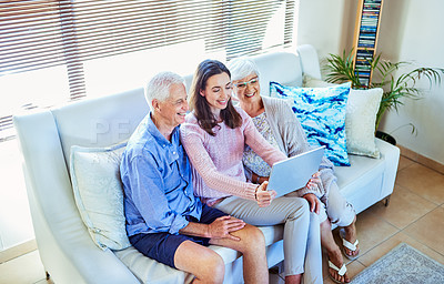 Buy stock photo Shot of a young woman using a digital tablet with her elderly parents at home