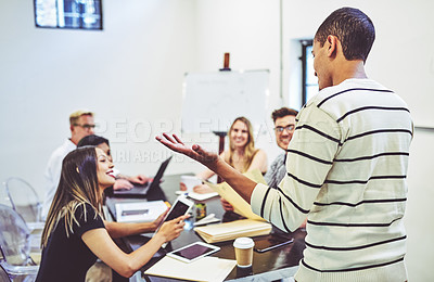 Buy stock photo Rearview shot of a businessman giving a presentation to his colleagues in an office