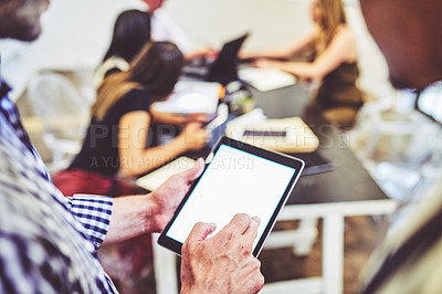Buy stock photo Closeup shot of two unrecognisable businessmen using a digital tablet in an office with their colleagues in the background
