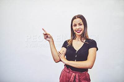 Buy stock photo Studio portrait of a young businesswoman pointing against a white background