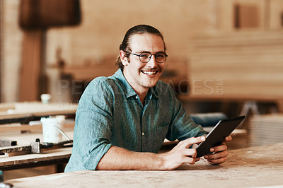 Buy stock photo Portrait of a young carpenter using a digital tablet while working inside his workshop