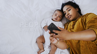 Buy stock photo Shot of a young woman taking a selfie with her adorable baby boy on the bed at home