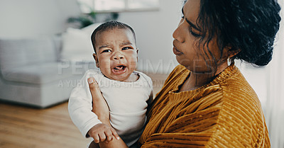 Buy stock photo Shot of a cute baby boy crying while his mother carries him at home