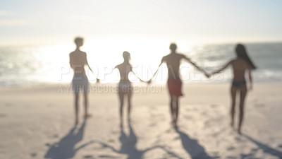 Buy stock photo Defocused rearview shot of a group of young people holding hands and enjoying themselves at the beach