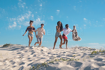 Buy stock photo Full length shot of a group of young friends running together and enjoying themselves on the beach