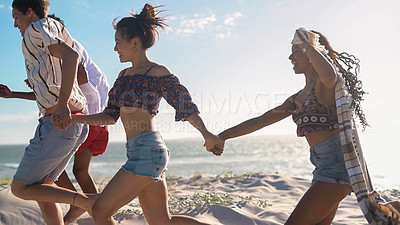 Buy stock photo Shot of a group of young friends running together and enjoying themselves on the beach