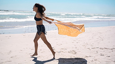 Buy stock photo Full length shot of an attractive young woman walking and enjoying herself on the beach