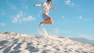 Buy stock photo Full length shot of energetic young man jumping high in the air while enjoying himself at the beach