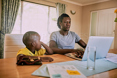 Buy stock photo Cropped shot of a young single father using a laptop while sitting with his son at home