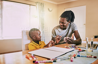 Buy stock photo Cropped shot of an affectionate young single father helping his son with his homework at home
