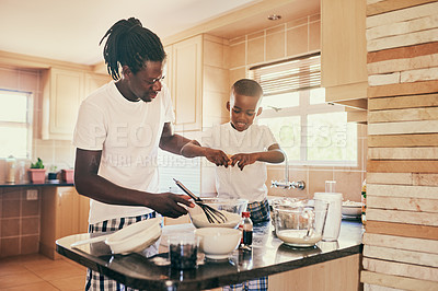 Buy stock photo Cropped shot of an adorable young boy cracking an egg while helping his father make breakfast at home