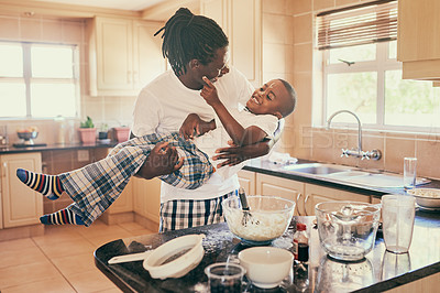 Buy stock photo Cropped shot of an affectionate father and son feeling playful while making breakfast at home together