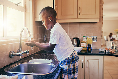 Buy stock photo Cropped shot of an adorable young boy standing by the kitchen sink and washing his hands before making breakfast