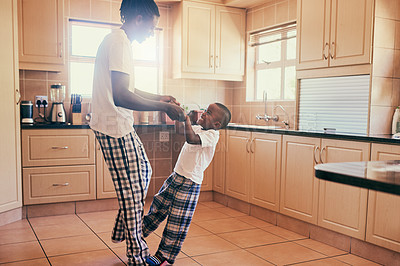 Buy stock photo Cropped shot of a happy young boy standing on his father's toes while they dance in their kitchen at home