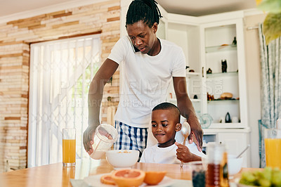 Buy stock photo Cropped shot of a handsome young man mixing his son's cereal while on the phone in his home