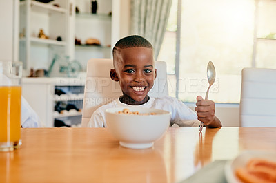 Buy stock photo Cropped portrait of a happy young boy about to eat his cereal for breakfast while sitting alone at the table