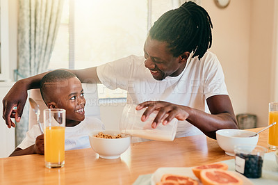 Buy stock photo Cropped shot of a handsome young man pouring milk into his son's cereal in their home