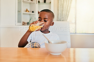 Buy stock photo Cropped shot of an adorable young boy sitting alone at the breakfast table and enjoying a glass of fruit juice