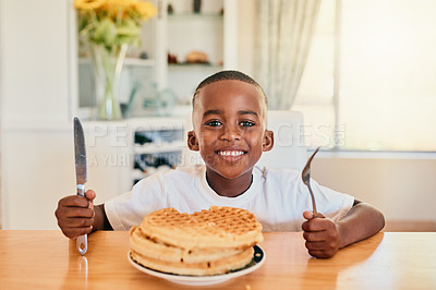 Buy stock photo Cropped portrait of a happy young boy sitting alone and having waffles for breakfast in his home