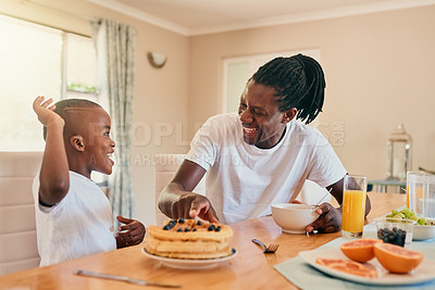 Buy stock photo Cropped shot of an adorable young boy sitting and having breakfast with his father at home