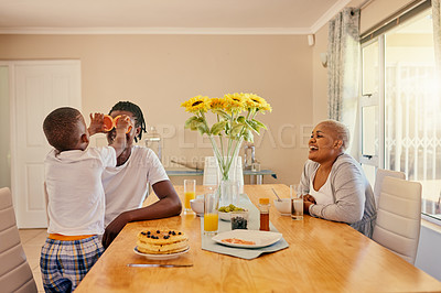 Buy stock photo Cropped shot of a playful young family bonding over breakfast during a weekend at home