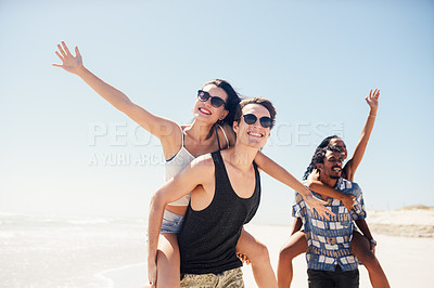 Buy stock photo Shot of two young couples enjoying themselves at the beach on a sunny day