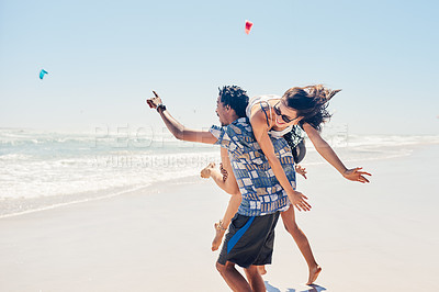 Buy stock photo Shot of a happy young couple spending the day at the beach