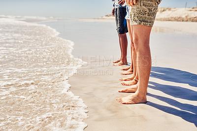 Buy stock photo Cropped shot of an unrecognizable group of friends standing with their feet in the sand