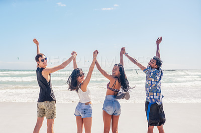 Buy stock photo Rearview shot of a group of friends standing with their arms raised