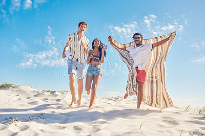 Buy stock photo Shot of three friends enjoying themselves at the beach on a sunny day