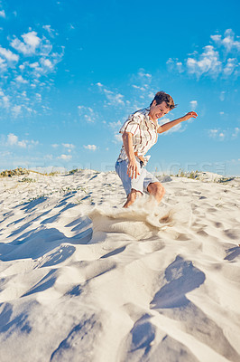 Buy stock photo Shot of a handsome young man having fun in the sand