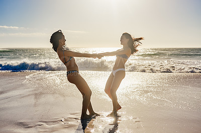 Buy stock photo Shot of two young women enjoying themselves at the beach on a sunny day