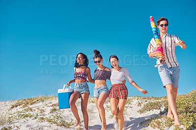 Buy stock photo Full length shot of a group of young friends heading out to have a picnic together at the beach