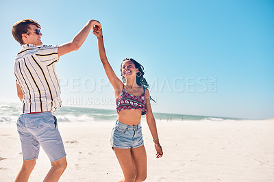 Buy stock photo Shot of a happy young couple dancing together on the beach