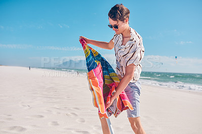 Buy stock photo Shot of a handsome young man setting up a beach umbrella on a sunny day at the beach