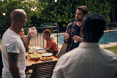 Buy stock photo Shot of a group of young men having drinks at a dinner party outdoors