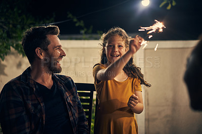 Buy stock photo Shot of an adorable little girl having fun with sparklers with her father in the garden at night
