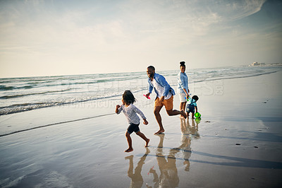 Buy stock photo Shot of a young family spending time together at the beach