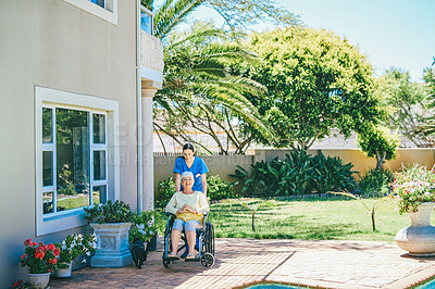 Buy stock photo Full length shot of an attractive young female nurse pushing a senior woman in a wheelchair outdoors at a nursing home