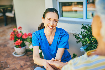 Buy stock photo Cropped shot of an attractive young female nurse chatting with a senior woman outdoors at a nursing home