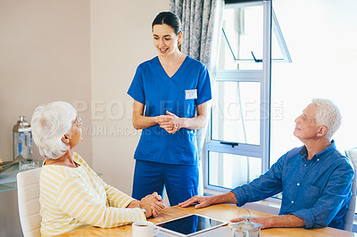 Buy stock photo Cropped shot of an attractive young female nurse having a chat with a senior couple in a nursing home