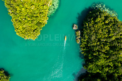 Buy stock photo High angle shot of a boat cruising around the beautiful green islands of Indonesia