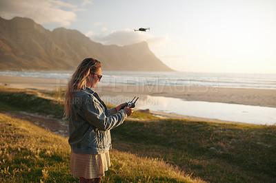 Buy stock photo Cropped shot of an attractive young woman flying a drone outdoors