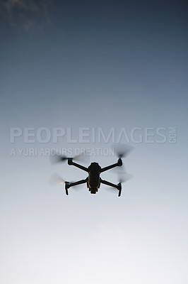 Buy stock photo Low angle shot of a drone flying high in the sky