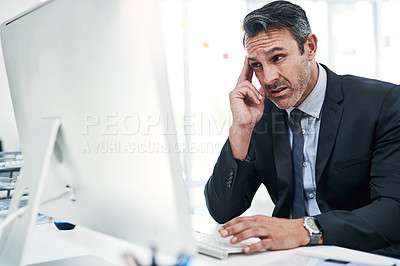 Buy stock photo Shot of a mature businessman looking stressed out while working on a computer in an office