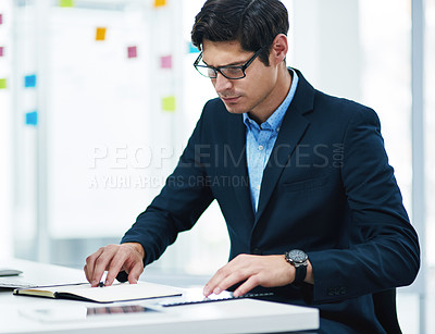 Buy stock photo Shot of a young businessman using a notebook in an office