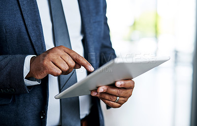 Buy stock photo Cropped shot of an unrecognizable businessman using a digital tablet while standing in a modern office