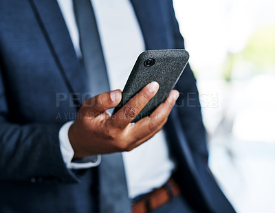 Buy stock photo Cropped shot of an unrecognizable businessman using a smartphone while standing in a modern office